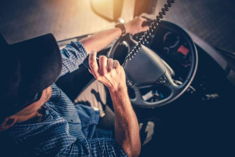 Truck driver in the driver seat talking on the CB radio.