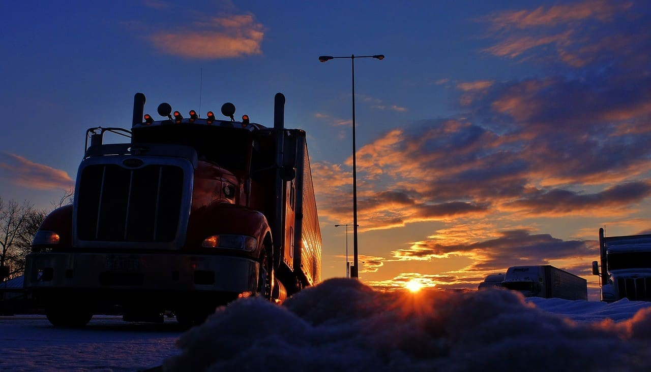 Trucks parked in the snow during a sunrise in the background.