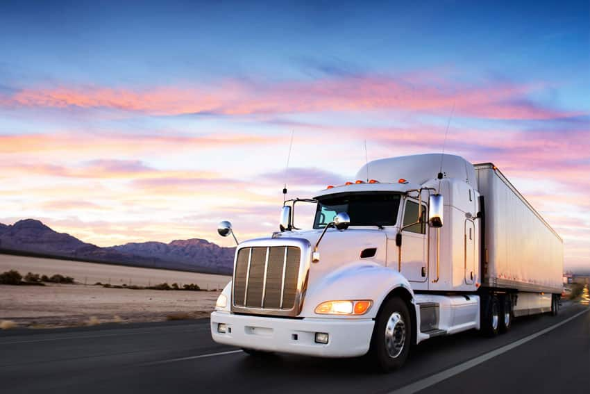 White semi truck with trailer against a colorful pink and blue sky.