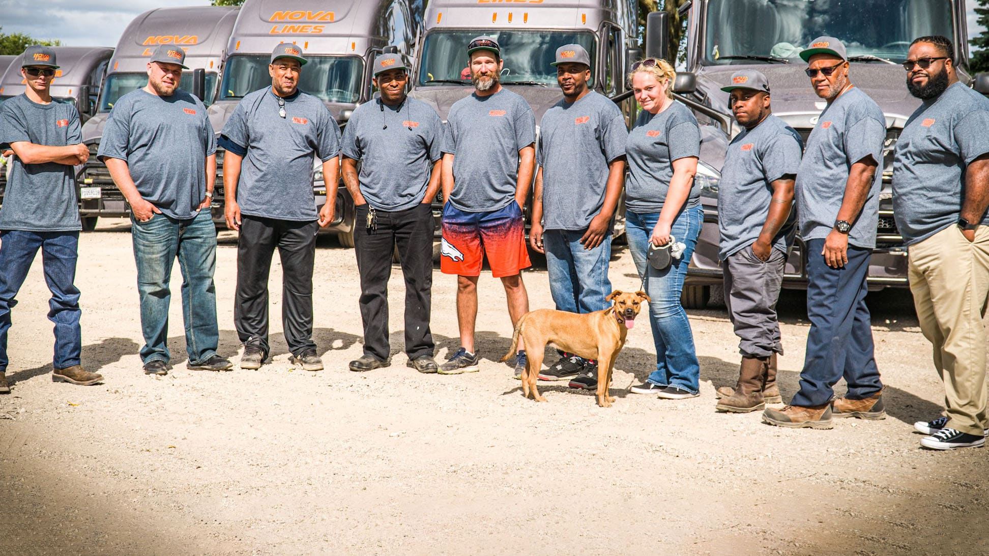 Ten Nova Lines truck drivers and one brown dog, lined up in front of their trucks.