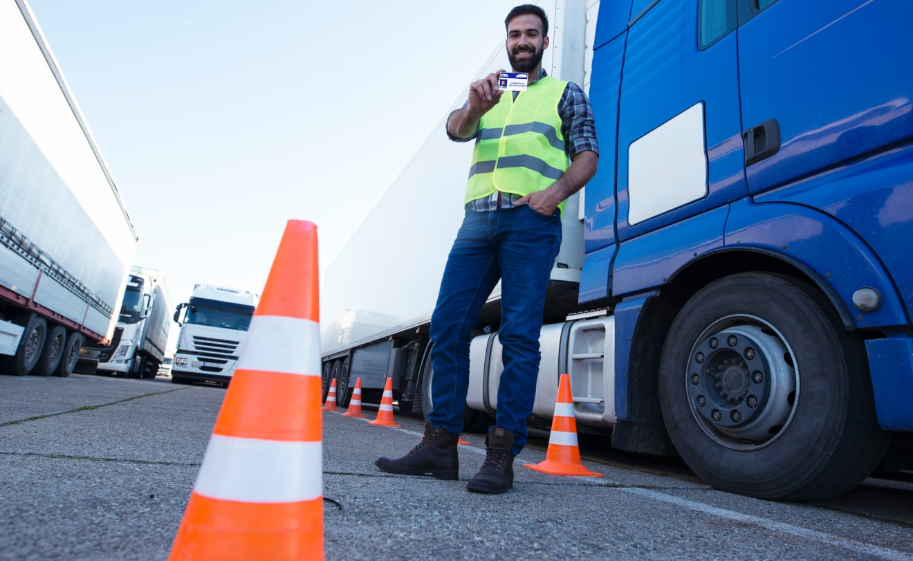 Man standing holding a CDL license and standing by his truck.