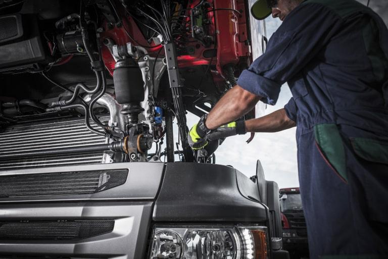 Diesel mechanic working on a lease purchase trucking company semi truck